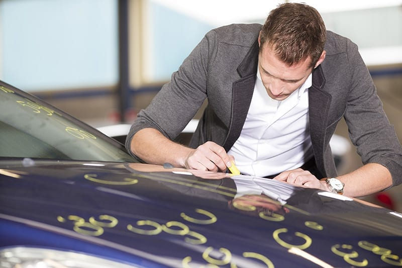A man marking spots on a car in need of hail damage repair
